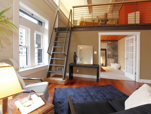 View of modern reconstructed living room with mezzanine area above bedroom. View of iron steep stairs